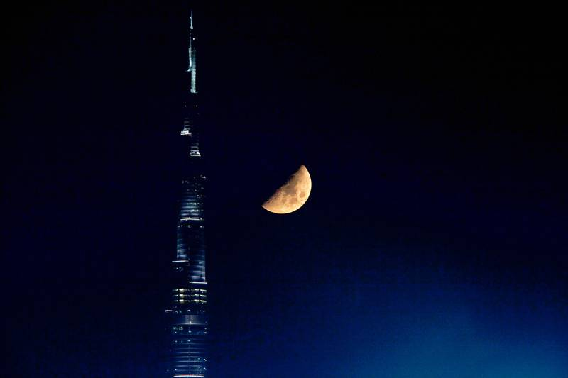 Dubai - August 16, 2010 - The moon in its first quarter phase begins to set as it appears close to the Burj Khalifa in Dubai, August 16, 2010. Neap tide, when the tide-generating forces of the sun and moon oppose each other they produce the smallest difference between high and low tide, which occurs during the first and third quarter phase of the moon. (Photo by Jeff Topping/The National) STOCK