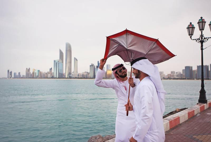 ABU DHABI - UNITED ARAB EMIRATES - 25MAR2013 - Ibrahim Khamis Obaid al Badwawi(R) and Mohamed Faraj al Mazrouei holds the umbrella from strong wind on the Corniche yesterday in Abu Dhabi. Ravindranath K / The National