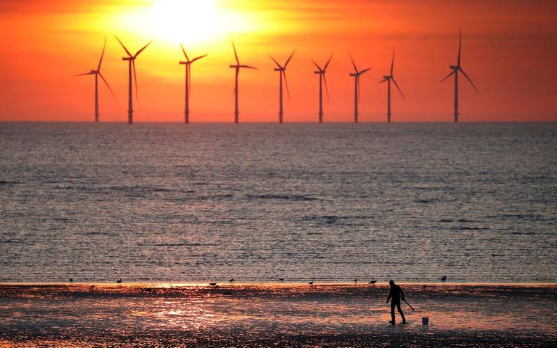 FILE PHOTO: A man stands on the beach as the sun sets behind the Burbo Bank wind farm near New Brighton, Britain, May 22, 2018. REUTERS/Phil Noble/File Photo