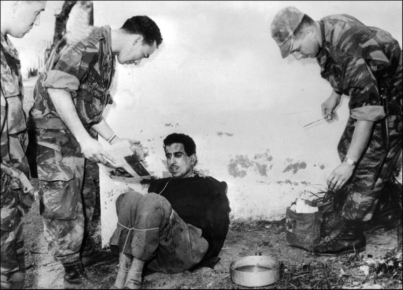 (FILES) In this file photo taken on March 14, 1957 French paratroopers question Algerian Omar Merouane in Saint Eugene.   French president Emmanuel Macron appointed expert historian Benjamin Stora to work on a report on the Algerian war and Colonisation memoir, a still burning issue, as the 60th anniversary of the independence of Algeria (1962) approaches. The report will be submitted on January 20, 2021. / AFP / INTERCONTINENTALE / Jacques GREVIN