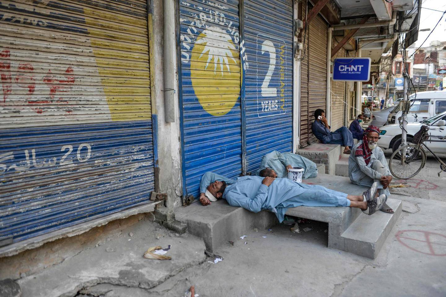 Labourers sleep near a market closed for the week-end in Rawalpindi on June 6, 2020.            / AFP / Farooq NAEEM