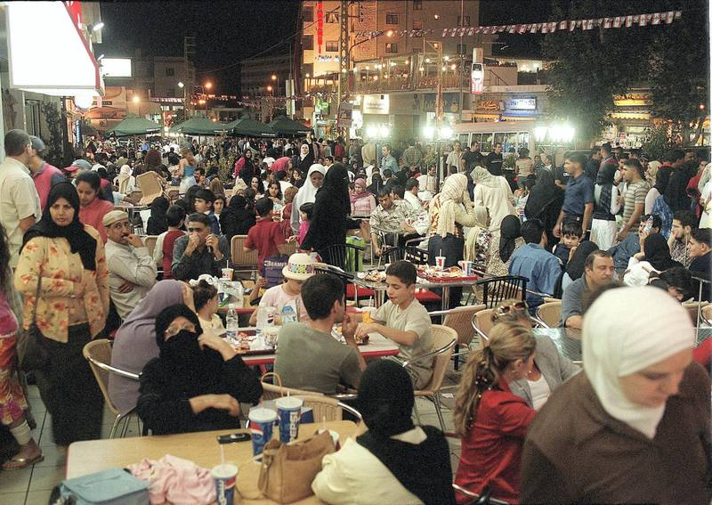 Lebanese and Arab tourists, mainly from the oil-rich Gulf states, eat outdoors in the Lebanese mountain resort of Bhamdoun, southeast of Beirut, 29 August 2002. The mountainous east Mediterranean country, seems to be regaining its pre-civil war status as the main tourist destination for rich Arabs, many of whom avoided Europe and the United States this year due to security restrictions, imposed mainly on visitors from Arab and Islamic countries, following the September 11 attacks which rocked New York and Washington in 2001. (Film) (Photo by JOSEPH BARRAK / AFP)