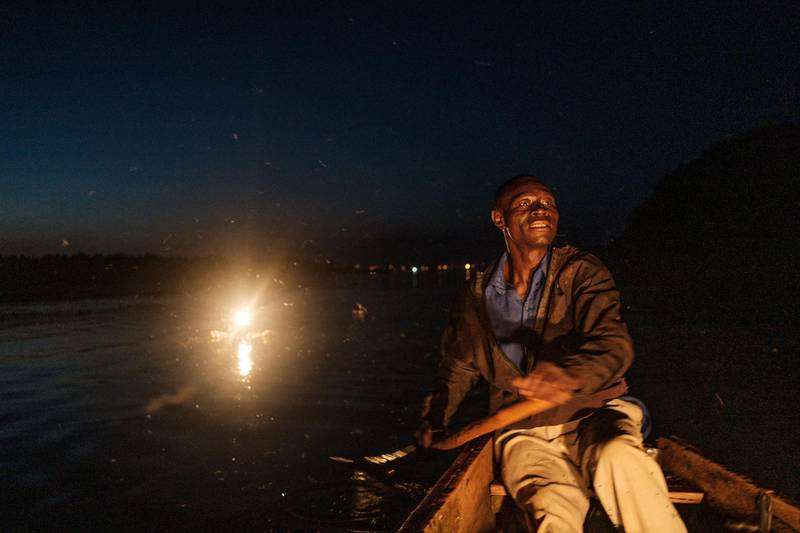 Mukasa rows his boat after setting up a kerosene lamp (behind him) which will eventually attract thousands of small silverfish on the Nile river, in Bujagali, Uganda, on November 12, 2020. - Fishermen in Uganda using more traditional fishing methods have been struggling to financially sustain themselves due to the lack of clients, which was caused by several lockdowns imposed to curb the spread of COVID-19 coronavirus since early March 2020. (Photo by Sumy Sadurni / AFP)