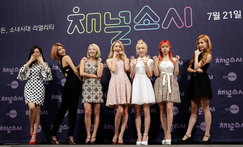 """FILE - In this July 21, 2015 file photo, South Korean girl group Girls' Generation pose for the media during a presentation to promote their new reality TV program """"Channel Girls' Generation"""" in Seoul, South Korea. The clothes, the hair, the confidence , the look of Korean pop-music, or K-pop, can either feel like high fashion or just plain quirky. But that's what draws in fans to South Korea's most famous export. It will be hard to bypass this cultural phenomenon during the upcoming 2018 Olympic Winter Games.(AP Photo/Lee Jin-man, File)"""
