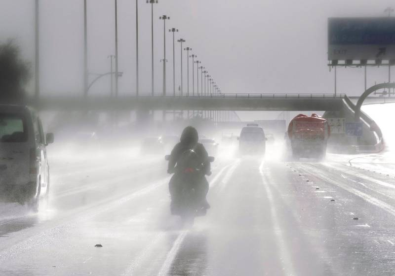 Abu Dhabi, United Arab Emirates, March 21, 2020.  A motorbike rider braves the slippery road on the Sheikh Zayed Bin Sultan Street during rainshowers.    Victor Besa / The National