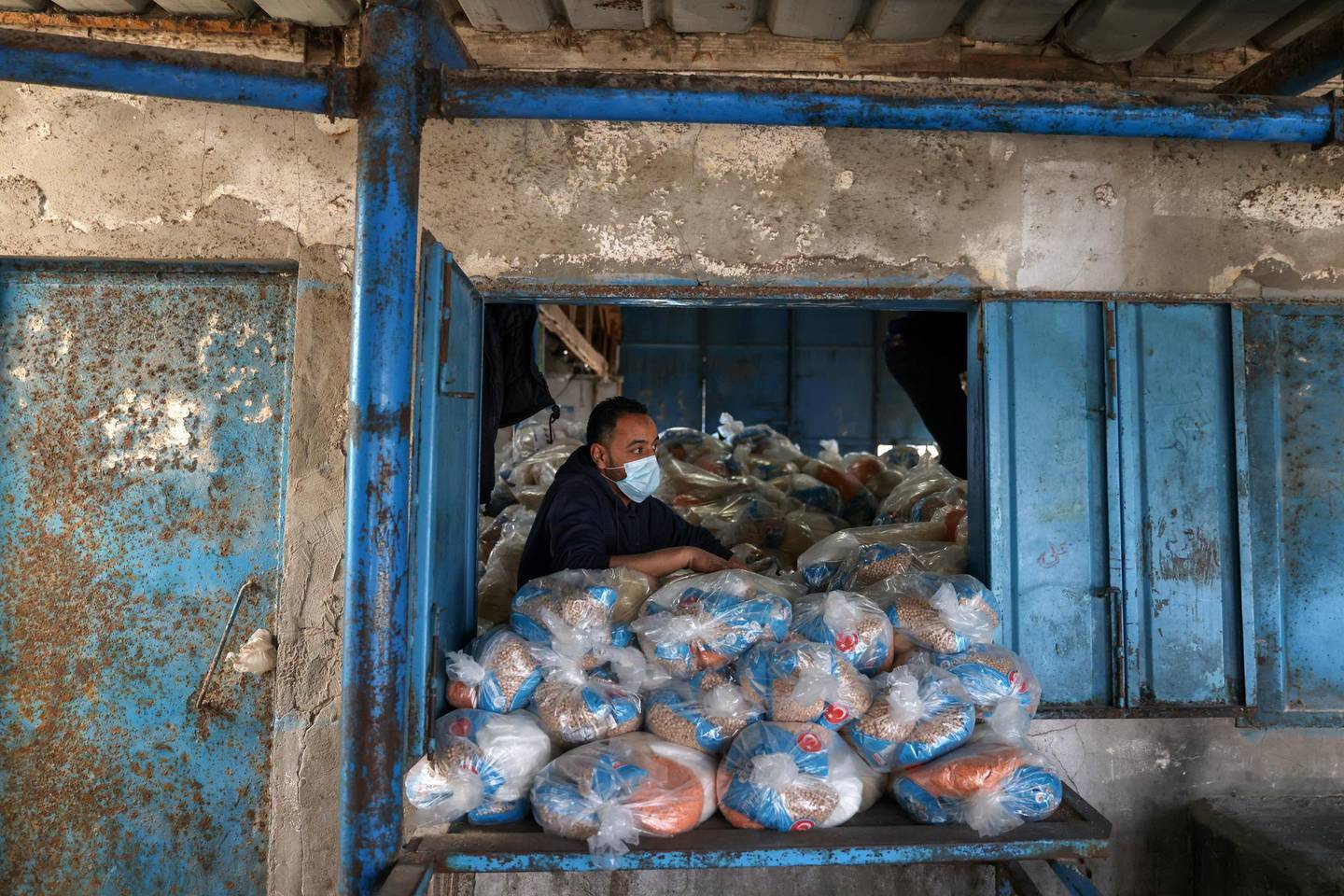 A Palestinian worker looks on as he prepares bags of food supplies at an aid distribution center run by United Nations Relief and Works Agency (UNRWA), at Beach refugee camp in Gaza City April 7, 2021. REUTERS/Mohammed Salem