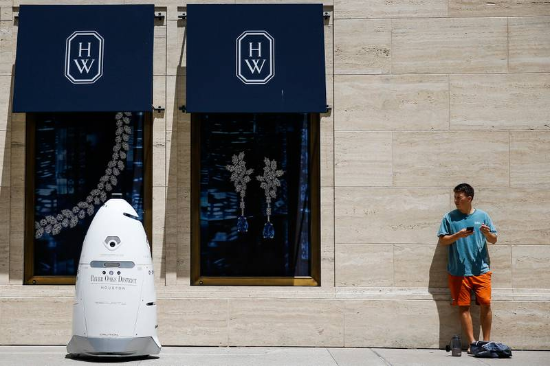 FILE - In this Friday, Aug. 18, 2017, file photo, a new security robot, nicknamed ROD2, drives toward Daniel Webb as it patrols the sidewalks and parking garage at River Oaks District in Houston. The robot recently became the latest addition to a patrol team eager to experiment with fast-evolving technology. According to a survey by the Pew Research Center, three-quarters of Americans say it is at least �������somewhat realistic������� that robots and computers will eventually perform most of the jobs currently done by people. Roughly the same proportion worry that such an outcome will have negative consequences, such as worsening inequality. (Michael Ciaglo/Houston Chronicle via AP, File)