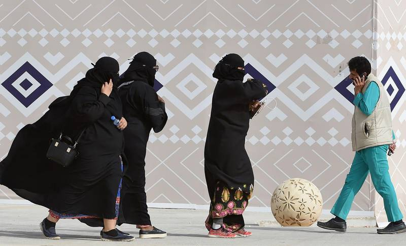 """A picture taken on January 19, 2018 shows Saudi women walking during the King Abdulaziz Camel Festival in Rumah, some 160 kilometres east of Riyadh. For decades the religious police, """"mutawa"""" as they are known, wielded unbridled powers as arbiters of morality, patrolling streets and malls to snare women wearing bright nail polish and chastise men seeking contact with the opposite sex. In recent years, Saudi Arabia launched a series of reforms, including gradually diminishing the mutawa's powers to arrest. Crown Prince Mohammed bin Salman has further cut back the political role of hardline clerics in a historic reordering of the Saudi state.  / AFP PHOTO / FAYEZ NURELDINE"""