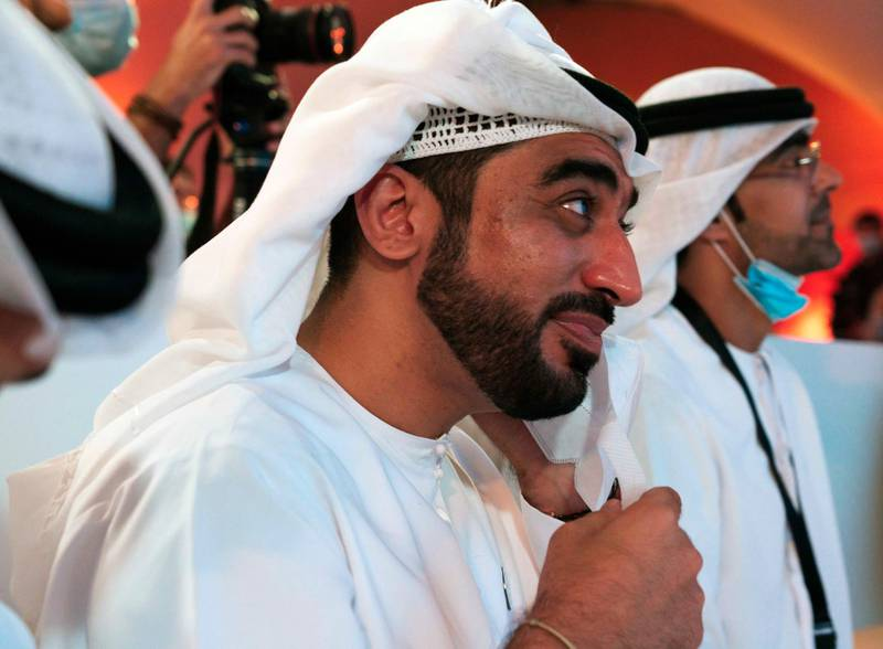 """An Emirati man wipes a tear away with his face mask due to the coronavirus pandemic while watching the launch of the """"Amal"""" or """"Hope"""" space probe at the Mohammed bin Rashid Space Center in Dubai, United Arab Emirates, Monday, July 20, 2020. A United Arab Emirates spacecraft, the """"Amal"""" or """"Hope"""" probe, blasted off to Mars from Japan early Monday, starting the Arab world's first interplanetary trip. (AP Photo/Jon Gambrell)"""