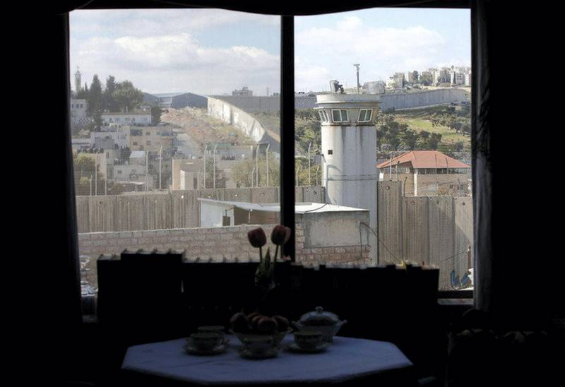 epa05830153 A view through a window from inside the Walled Off Hotel by British street artist Banksy in the West Bank city of Bethlehem, 04 March 2017. The hotel in the Palestinian territories is placed only a couple of meters from Israel's separation wall with all rooms facing it. The Walled Off Hotel will open for guests on 20 March, with bookings via the website.  EPA/ABED AL HASHLAMOUN *** Local Caption *** 53369059