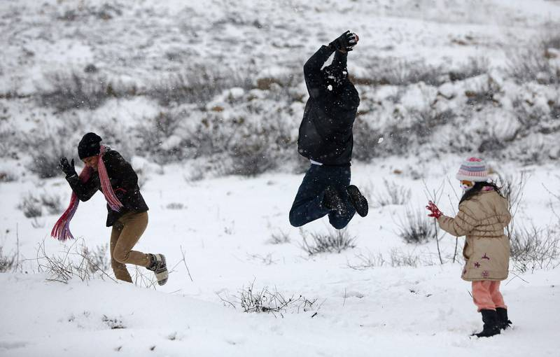 Palestinians play in the snow in the West Bank city of Ramallah January 10, 2013. At least 17 people have died due to a storm in Lebanon, Jordan, Turkey, Israel and the Palestinian territories. Meteorological agencies in Israel and Lebanon both called it the worst storm in 20 years. REUTERS/Mohamad Torokman (WEST BANK - Tags: ENVIRONMENT)