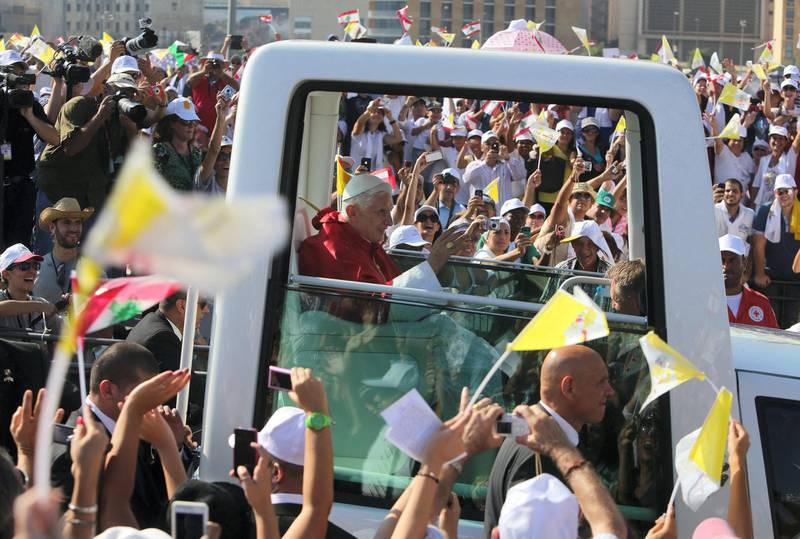 Pope Benedict XVI waves to the crowd from his popemobile as he arrives to lead an open-air mass in Beirut's waterfront on September 16, 2012, on the final day of his visit to Lebanon. Pope prayed that leaders in the Middle East work toward peace and reconciliation, in his homily at an open-air mass where an estimated 350,000 people attend. AFP PHOTO/JOSEPH EID (Photo by JOSEPH EID / AFP)