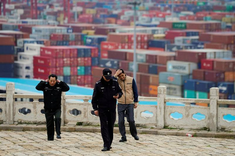FILE PHOTO: Security guards walk in front of containers at the Yangshan Deep Water Port in Shanghai, China April 24, 2018. REUTERS/Aly Song/File Photo