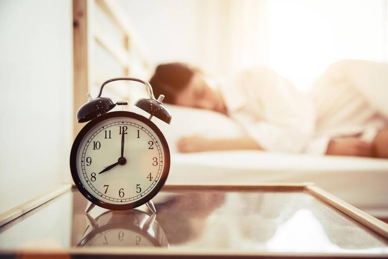 Alarm clock with beauty woman in background. Morning and Lazy time concept. Bedroom theme. Getty Images