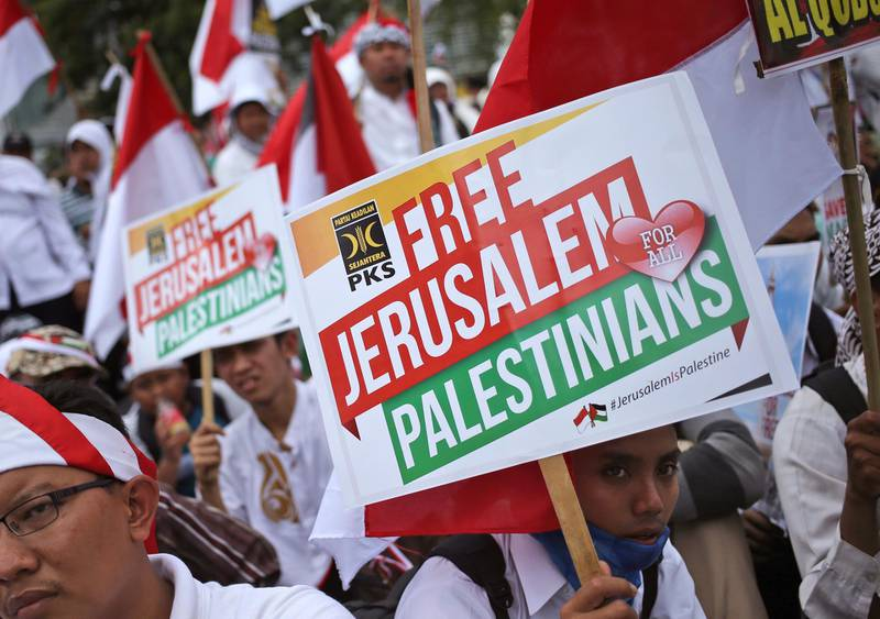Muslim men hold posters during a rally against President Donald Trump's decision to recognize Jerusalem as Israel's capital outside the U.S. Embassy in Jakarta, Indonesia, Sunday, Dec. 10, 2017. Hundreds of people across the most populous Muslim country staged protests Friday against Trump administration's policy shift on the contested city. (AP Photo/Dita Alangkara)