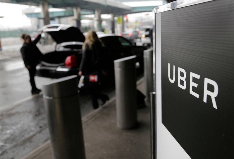 FILE - In this March 15, 2017, file photo, a sign marks a pick up point for the Uber car service at LaGuardia Airport in New York. Ride-hailing giant Uber has filed confidential preliminary paperwork for selling stock to the public. That's according to a report late Friday, Dec. 7, 2018 in the Wall Street Journal. (AP Photo/Seth Wenig, File)