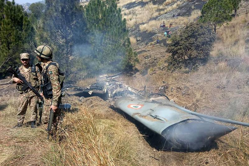 TOPSHOT - Pakistani soldiers stand next to what Pakistan says is the wreckage of an Indian fighter jet shot down in Pakistan controled Kashmir at Somani area in Bhimbar district near the Line of Control on February 27, 2019. Pakistan said on February 27 it shot down two Indian warplanes in its airspace over disputed Kashmir, in a dramatic escalation of a confrontation that has ignited fears of an all-out conflict between the nuclear-armed neighbours. / AFP / STR