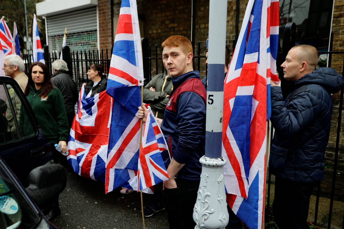 People hold the Union Flag whilst attending a Britain First rally as deputy leader Jayda Fransen (L) looks on, in Rochester, Britain November 15, 2014. Picture taken November 15, 2014.   REUTERS/Kevin Coombs