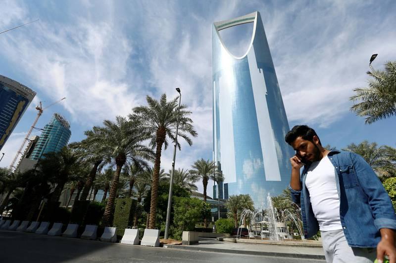 FILE PHOTO: A man speaks on the phone as he walks past the Kingdom Centre Tower in Riyadh, Saudi Arabia, November 5, 2017. REUTERS/Faisal Al Nasser - /File Photo