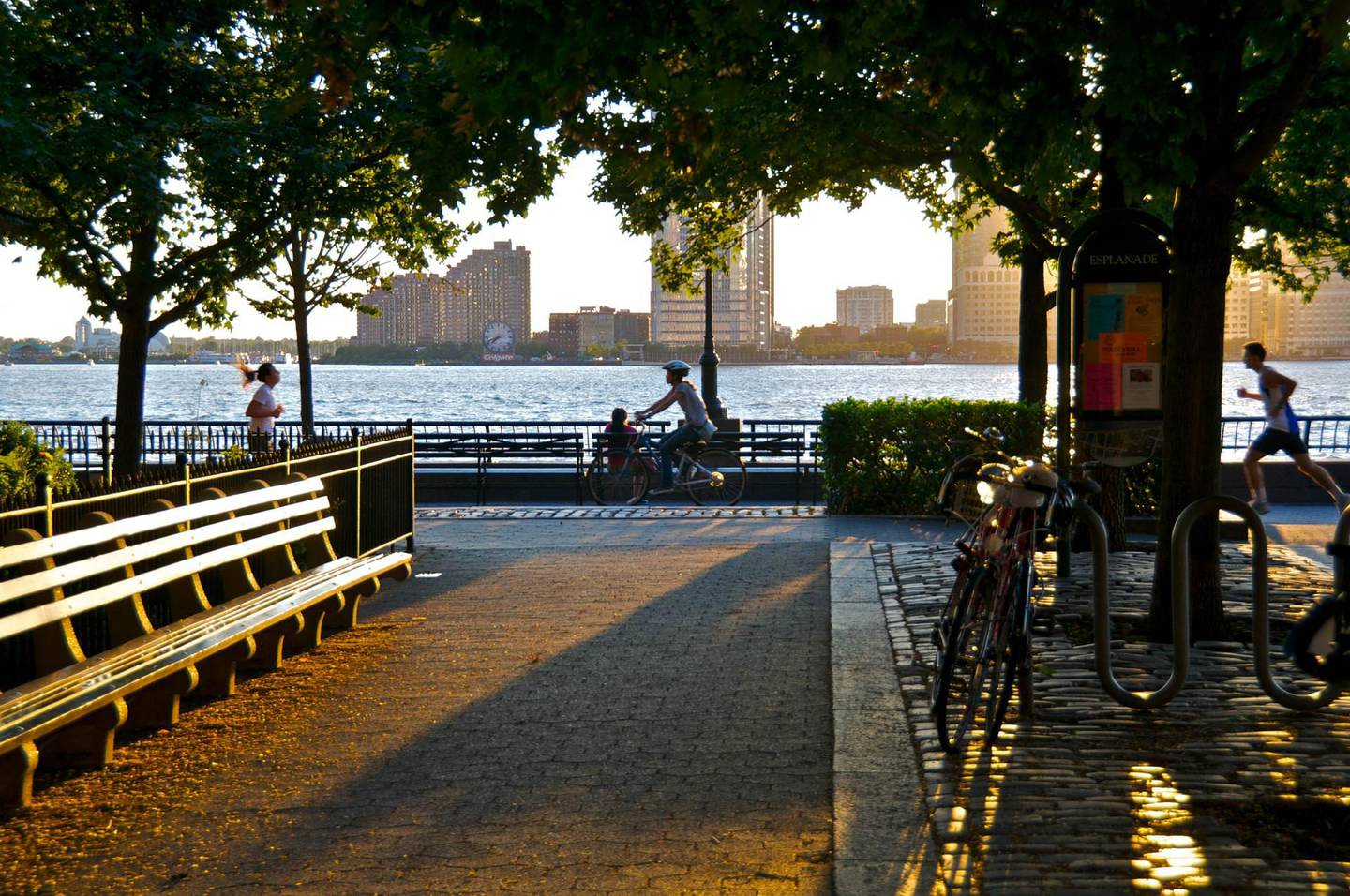 """""""New York City, USA - August 18, 2012: A bicyclist  and runners are seen passing by a woman sitting along the Battery Park City Promenade during a summer sunset over the Hudson River, Lower Manhattan."""" Getty Images"""