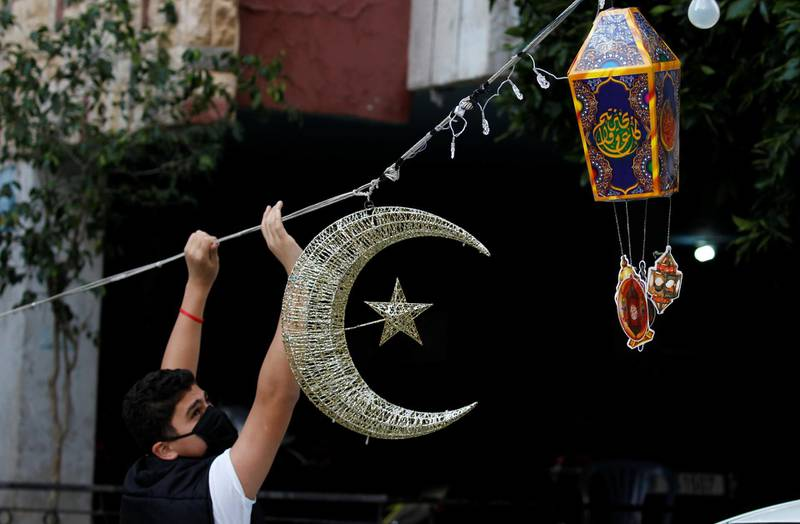 A man puts Ramadan decorations on a street ahead of the Muslim holy month of Ramadan, during a countrywide lockdown over the coronavirus disease (COVID-19) in Beirut, Lebanon April 19, 2020. Picture taken April 19, 2020. REUTERS/Mohamed Azakir
