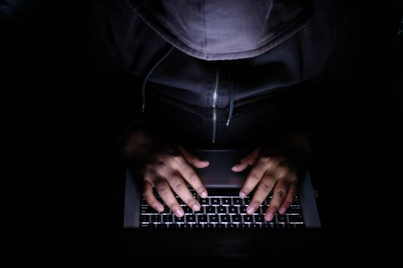 Man behind laptop, man hacker, laptop on desk. Getty Images