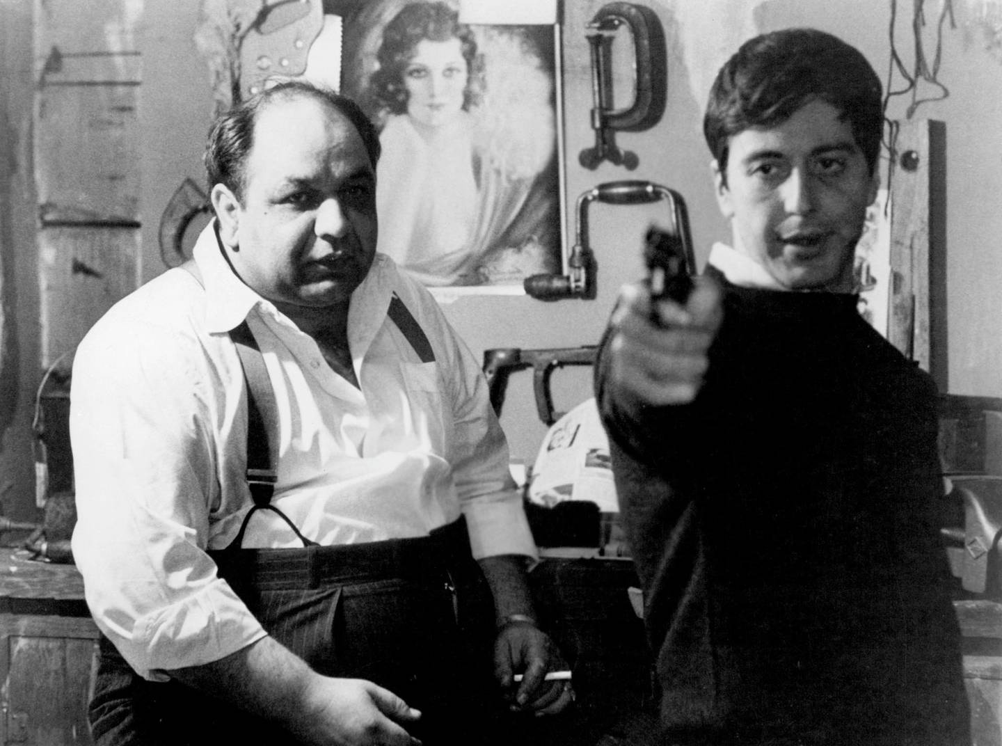 Richard S Castellano watching Al Pacino aim gun in a scene from the film 'The Godfather', 1972. (Photo by Paramount/Getty Images)