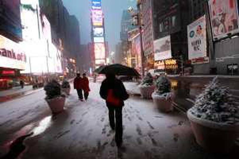 Early morning pedestrians walk in New York's Times Square, Wednesday, Feb. 10, 2010. A blizzard is expected to drop 10 to 15 inches (25 to 38 cm) of snow on the metropolitan area Wednesday. (AP Photo/Mark Lennihan)