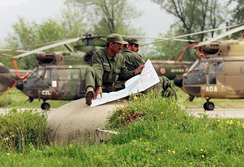 Soldiers from the United Arab Emirates sit atop a pillbox reading a map at the NATO humanitarian base at the Tirana Airport  28 April, 1999 in Albania.  The UAE Air Force flies 4 helicopter-missions a day to bring aid to Kosovar refugees in northern Albania.   (ELECTRONIC IMAGE)   AFP PHOTO    Mike NELSON/mn (Photo by MIKE NELSON / AFP)