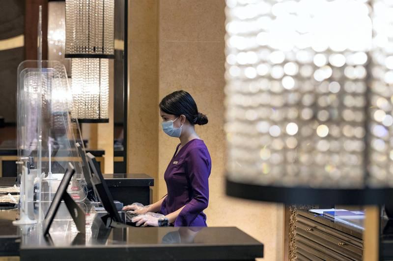 Dubai, United Arab Emirates - Reporter: N/A. Standalone. Covid-19/Coronavirus. Janel works behind a plastic partition at the H Hotel reception in Dubai. Thursday, August 27th, 2020. Dubai. Chris Whiteoak / The National