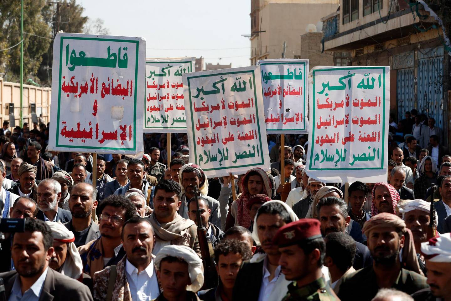 epa08950864 Yemenis hold up banners reading in Arabic 'Allah is the greatest of all, Death to America, Death to Israel, A curse on the Jews, Victory to Islam' during an anti-US protest in Sana'a, Yemen, 20 January 2021. According to reports, US Secretary of State Tony Blinken has pledged to immediately review the US terrorist designation of Yemen's Houthi movement a day after Donald Trump's government designated it as a Foreign Terrorist Organization (FTO).  EPA/YAHYA ARHAB