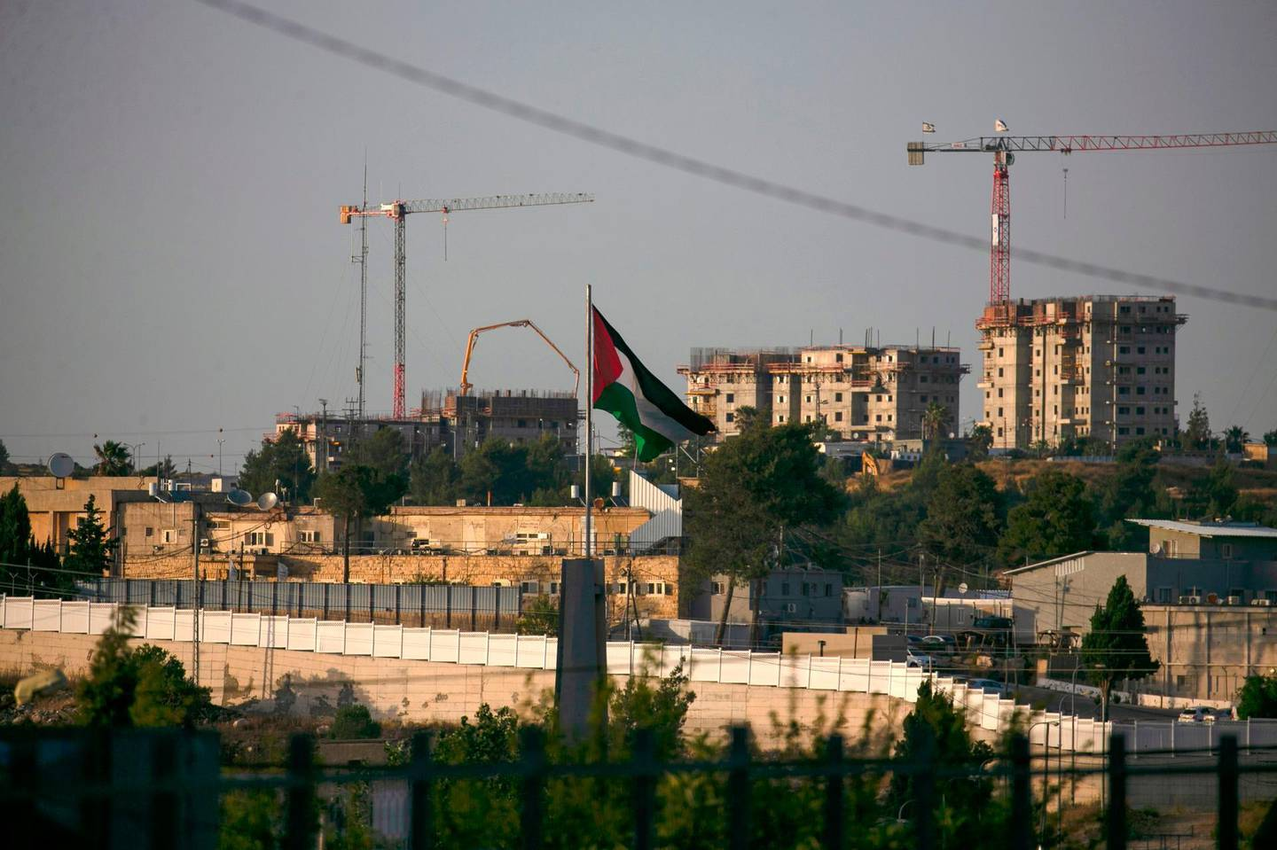 A Palestinian flag waves at the northern entrance to the city of Ramallah in the occupied West Bank as construction works take place in the Israeli settlement of Beit El in the background, on June 16, 2020. Israel intends to annex West Bank settlements and the Jordan Valley, as proposed by US President Donald Trump, with initial steps slated to begin from July 1. / AFP / ABBAS MOMANI