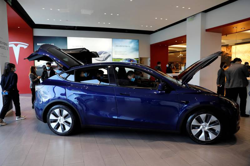 FILE PHOTO: Visitors wearing face masks check a China-made Tesla Model Y sport utility vehicle (SUV) at the electric vehicle maker's showroom in Beijing, China January 5, 2021. REUTERS/Tingshu Wang/File Photo
