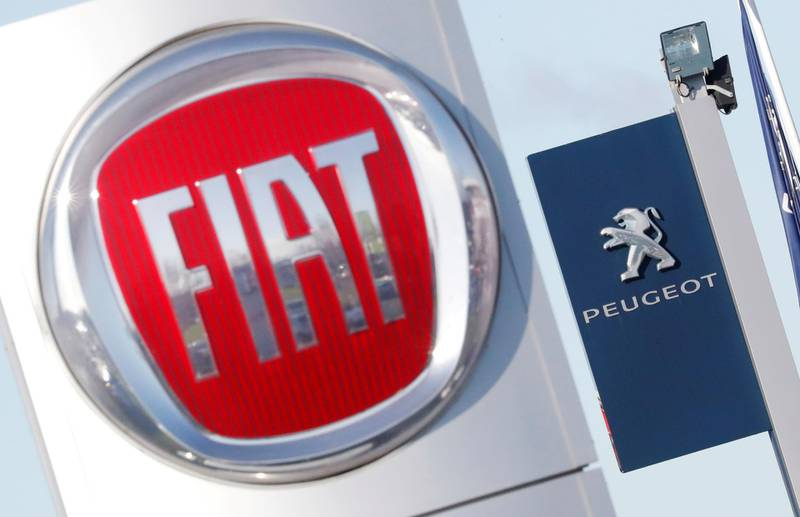 FILE PHOTO: The logos of car manufacturers Fiat and Peugeot are seen in front of dealerships of the companies in Saint-Nazaire, France, November 8, 2019. REUTERS/Stephane Mahe/File Photo