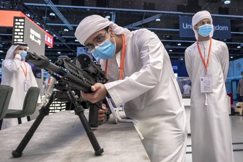 Abu Dhabi, United Arab Emirates, February 24, 2021.  Idex 2021 Day 4.Visitors look at  the 817 DMR  Semi-Automatic Marksman Rifle at the Caracal stand. Victor Besa / The NationalSection:  NA