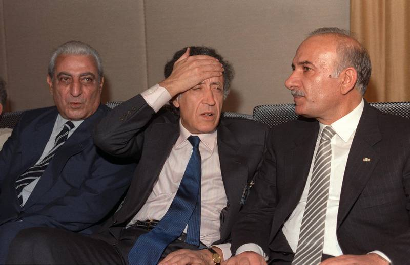 Sitting between Lebanese Parliament speaker Hussain al-Hussaini (R) and deputy Abdelallah Rassi (L), the Arab League envoy, Algerian Lakhdar Ibrahimi puts his hand on his forehead 29 September 1989 in Taif after the members of Lebanese National Assembly started to discuss the charter of national reconciliation. The session was attended by 31 Christian and 31 Muslim MP's. At a further meeting 22 October 1989, the charter of national reconciliation (the Taif Agreement) was endorsed by 58 of the 62 deputies attending the session. The Taif agreement provided for the transfer of executive power from the presidency to a cabinet, with portfolios divided equally among Christian and Muslim ministers. (Photo by NABIL ISMAIL / AFP)