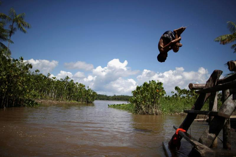 A child jumps in Ilha da Salvacao river, at the riverside community Galileia, as healthcare workers visit riverside communities to check on residents during the coronavirus disease (COVID-19) outbreak, in the municipality of Melgaco, at Marajo island, Para state, Brazil, June 4, 2020. Picture taken June 4, 2020. REUTERS/Ueslei Marcelino