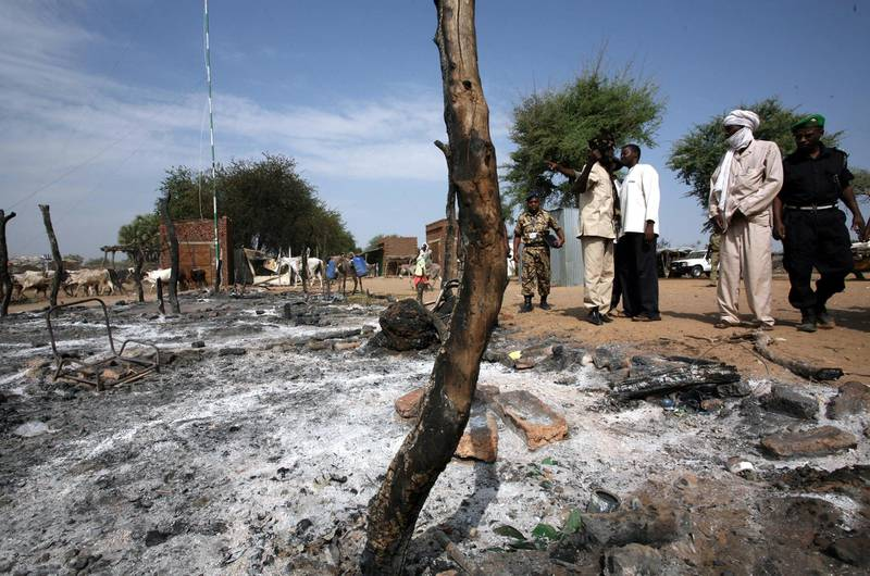 An African Union Mission in the Sudan (AMIS) military observer (L) and Sudan Liberation Army (SLA) members survey the burnt-out marketplace in Muhajariya town in southern Darfur, 10 October 2007, following violent clashes. The town, which is a stronghold of the SLA Minni Minnawi faction, the only rebel group to sign the May 2006 Darfur Peace Agreement, experienced heavy fighting 09 October in what the SLA said was a Sudanese government-backed attack in which more than 50 people died. The clashes left many homes burnt to the ground and shops destroyed and looted. The UN said 10 October that fighting had erupted elsewhere in Darfur between the SLA and the Sudanese army. AFP PHOTO/HO/AMIS/STUART PRICE. (Photo by AMIS / AFP)