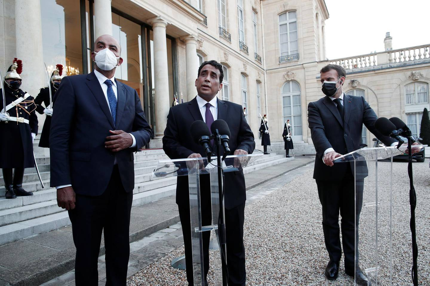 French President Emmanuel Macron, wearing a protective face mask, talks to the press with Mohamed al-Menfi, Head of the Presidential Council of Libya and Musa al-Koni, Vice-President of the Presidential Council of Libya after a meeting at the Elysee Palace in Paris, France, March 23, 2021. REUTERS/Benoit Tessier