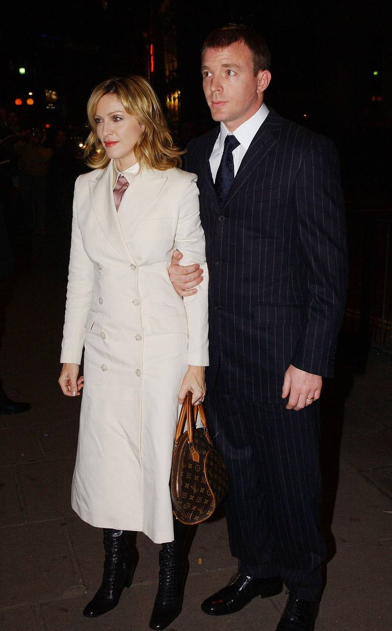 400284 01: Singer and actress Madonna and her husband and film director Guy Ritchie arrive at the opening of the Mario Testino photography exhibition January 29, 2002 at the National Portrait Gallery in London. The exhibition is a retrospective of celebrity portraiture by the acclaimed fashion photographer who has worked for all of the top fashion magazines and shot campaigns for a number of leading fashion houses. 150 works are on display, selected by Testino himself, including prints of Kate Moss, Robbie Williams, John Galliano and Princess Diana. (Photo by Anthony Harvey/Getty Images)