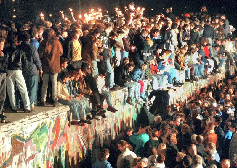 """This photo taken on November 11, 1989 in Berlin shows young East Berliners celebrating atop the Berlin Wall. - The fall of the Berlin Wall in 1989, when thousands of Germans joyfully danced atop its graffiti-covered remains, to some heralded the """"end of history"""" in a globalised world. Thirty years later, the return of hard frontiers made of bricks, concrete and razor wire symbolises stark new political realities that are a far cry from the West's heady optimism in the era when the Soviet bloc imploded. (Photo by STR / dpa / AFP) / Germany OUT"""