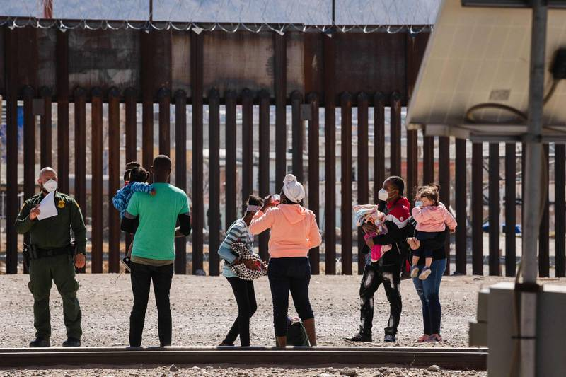 """Border Patrol agents apprehend a group of migrants near downtown El Paso, Texas following the congressional border delegation visit on March 15, 2021. President Joe Biden faced mounting pressure Monday from Republicans over his handling of a surge in migrants -- including thousands of unaccompanied children -- arriving at the US-Mexican border. Republican Congressman Kevin McCarthy of California, who leads his party in the House of Representatives, told reporters last week the """"crisis at the border is spiraling out of control.""""""""It's entirely caused by the actions of this administration,"""" said McCarthy.  / AFP / Justin Hamel"""