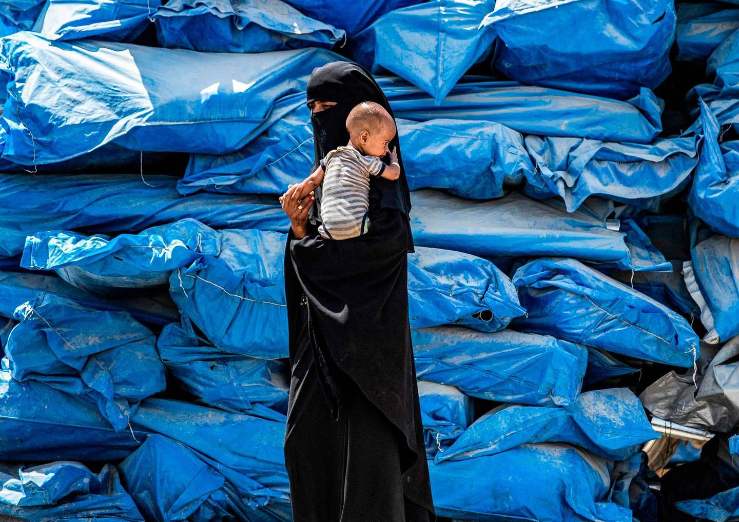 TOPSHOT - A woman wearing a niqab (full face veil) walks carrying an infant at al-Hol camp for displaced people in al-Hasakeh governorate in northeastern Syria on July 22, 2019, as people collect UN-provided humanitarian aid packages.  / AFP / Delil souleiman