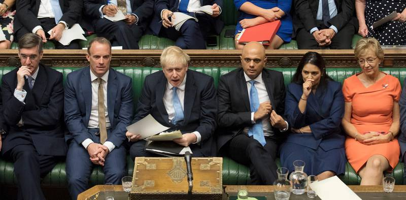 In this image released by the House of Commons, new British Prime Minister Boris Johnson, third left, sits with his front bench and other Conservative lawmakers in Parliament in London, Thursday, July 25, 2019. From left they are: Jacob Rees-Mogg, Dominic Raab, Johnson, Sajid Javid, Priti Patel and Andrea Leadsom. (Jessica Taylor/House of Commons via AP)