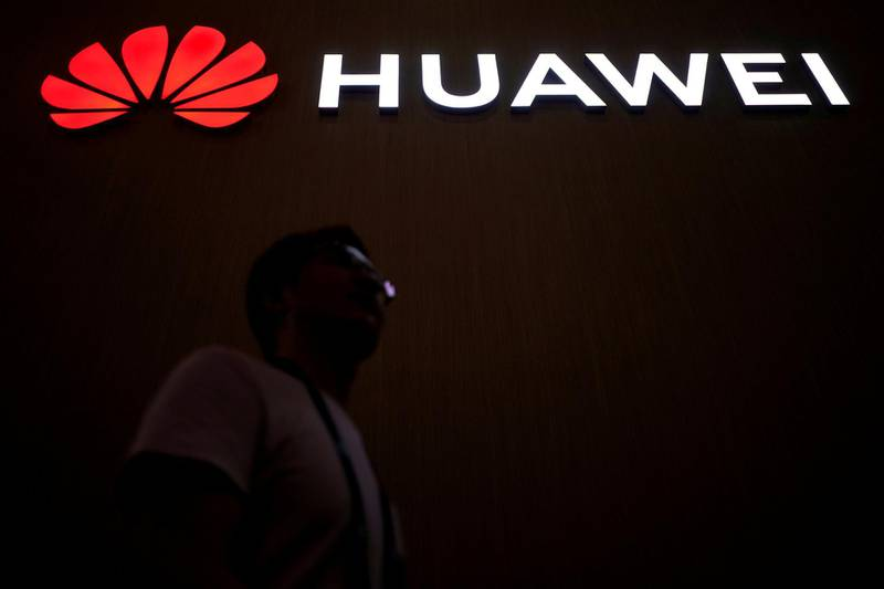 FILE PHOTO: A man walks past a sign board of Huawei at CES (Consumer Electronics Show) Asia 2018 in Shanghai, China June 14, 2018. REUTERS/Aly Song/File Photo