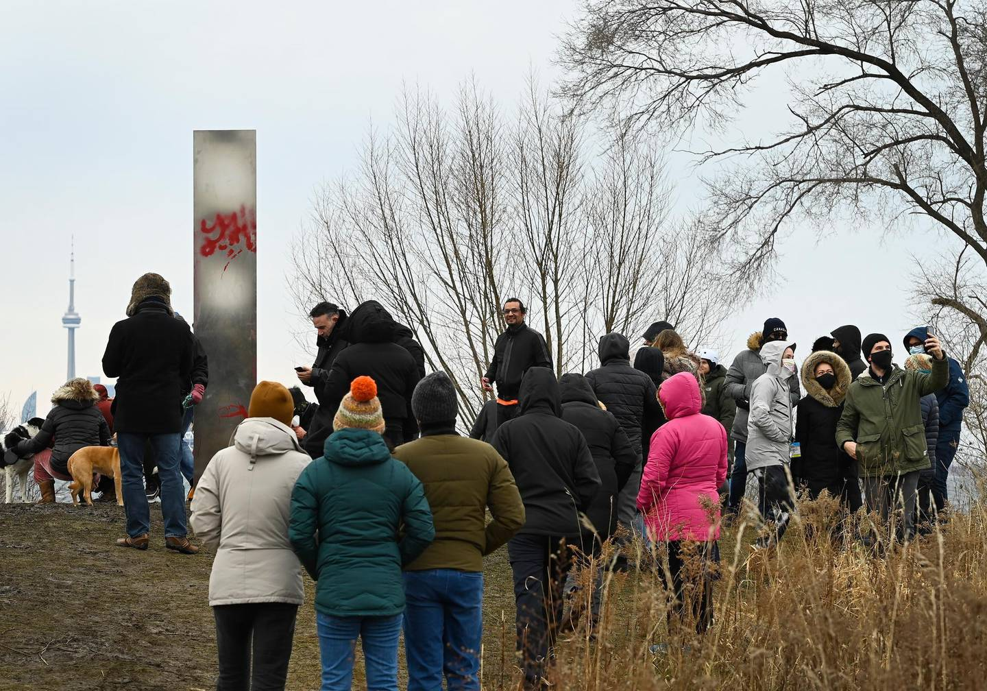 People look at a metallic monolith that appeared on the shorelines of Humber Bay Park during the COVID-19 pandemic in Toronto on Friday, Jan. 1, 2021. (Nathan Denette/The Canadian Press via AP)