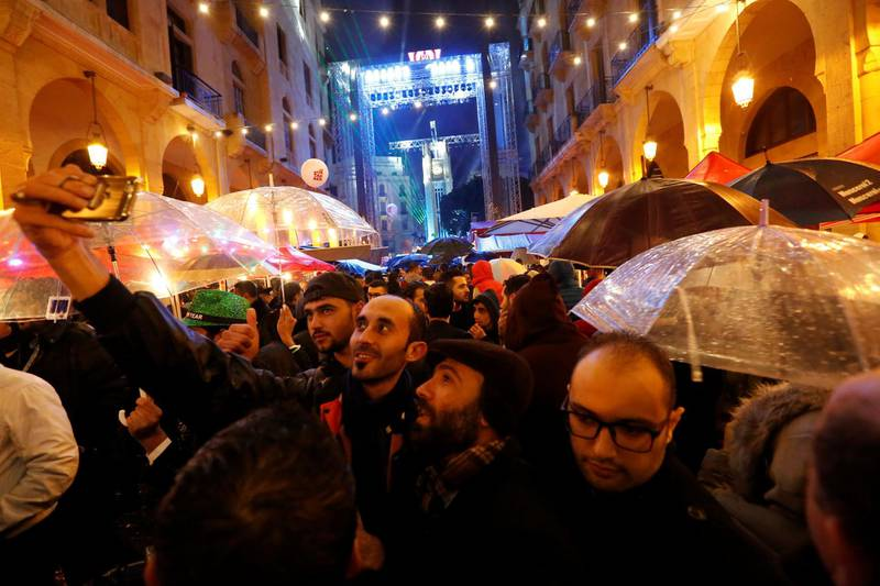 People take selfies as they celebrate in the rain ahead of the New Year at down town Beirut,Lebanon December 31, 2017. REUTERS/ Jamal Saidi