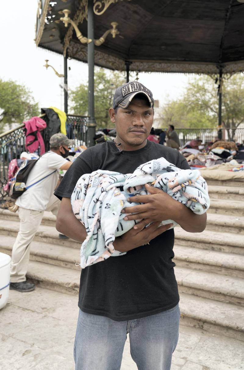 Fidelis Guzman holds his 9 day old child at Plaza Las Americas in Reynosa Mexico. Mr Guzman hopes to file asylum in the US. Willy Lowry/ The National