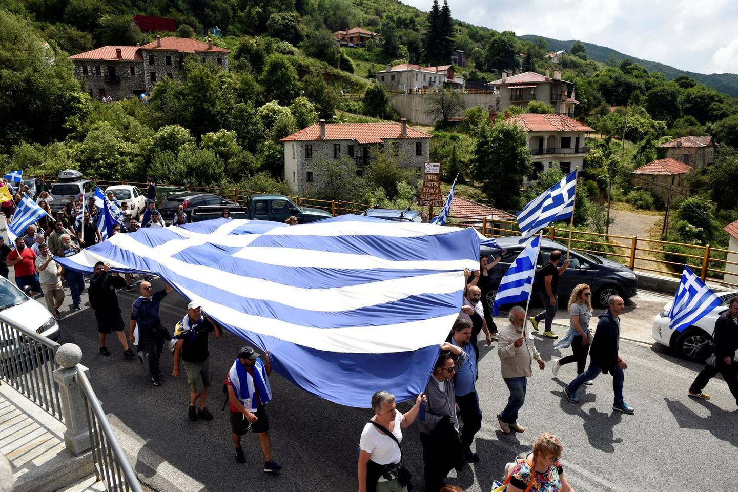 Protesters carry a giant Greek national flag during a demonstration against the agreement reached by Greece and Macedonia to resolve a dispute over the former Yugoslav republic's name, in Pisoderi village, northern Greece, June 17, 2018. REUTERS/Alexandros Avramidis