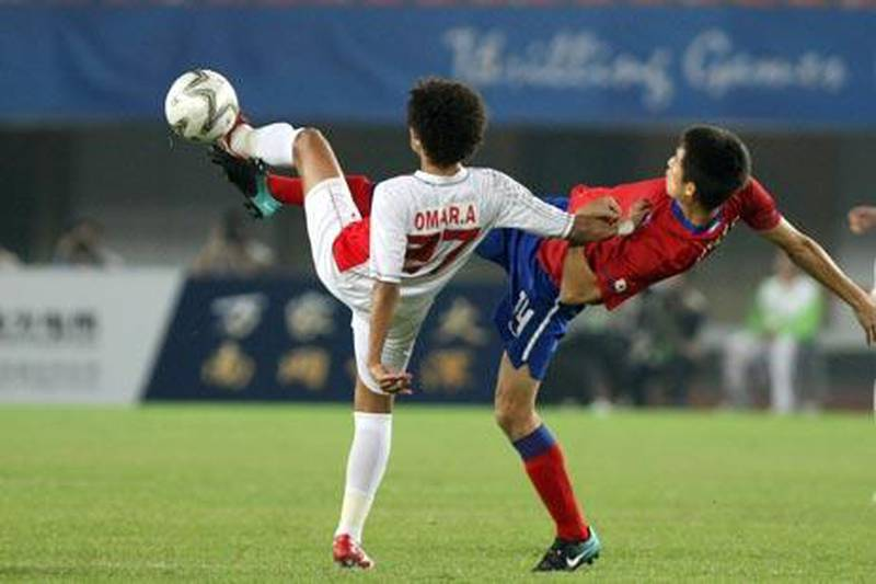Omar Abdulrahman al-Amoudi (L) of United Arab Emirates fights for the ball with Kim Jung-Woo of South Korea during the men's semi-final match at the 16th Asian Games in Guangzhou on November 23, 2010.  AFP PHOTO